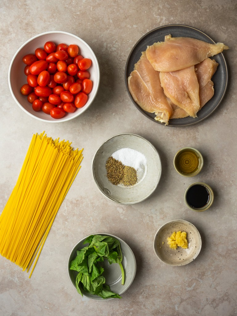 Above view of ingredients for cherry tomato pasta sauce with seared chicken