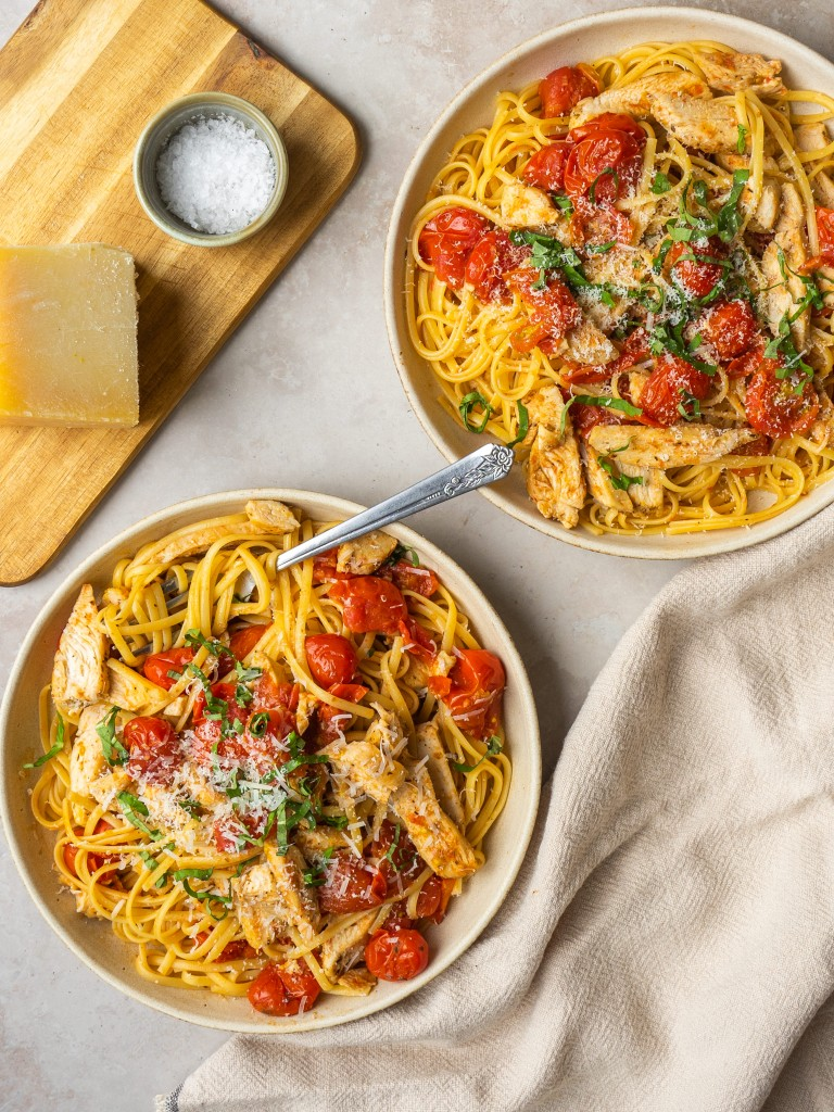 Above view of cherry tomato pasta sauce in serving bowls with parmesan cheese
