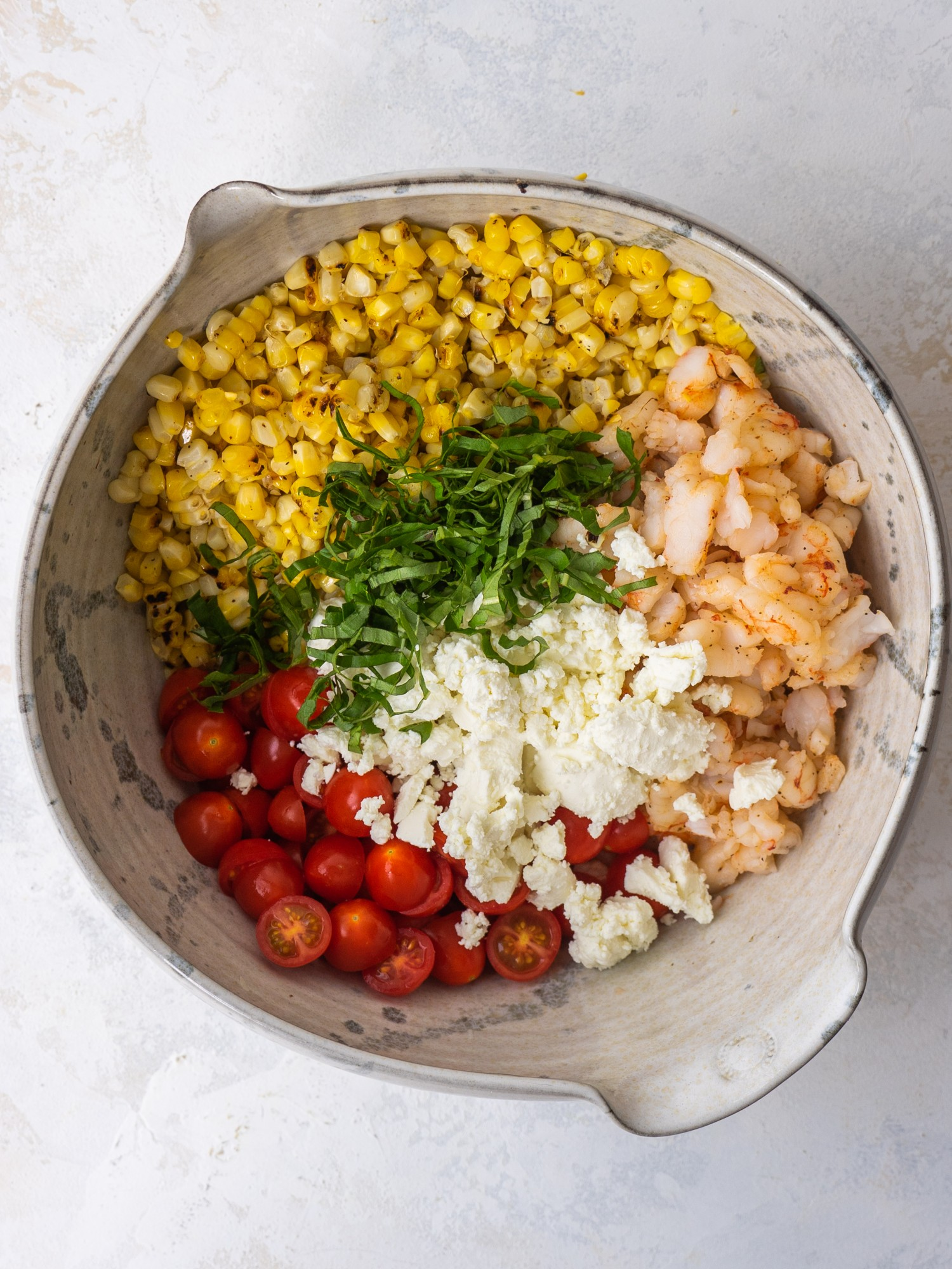 Above view of ingredients for creamy grilled shrimp salad in a mixing bowl