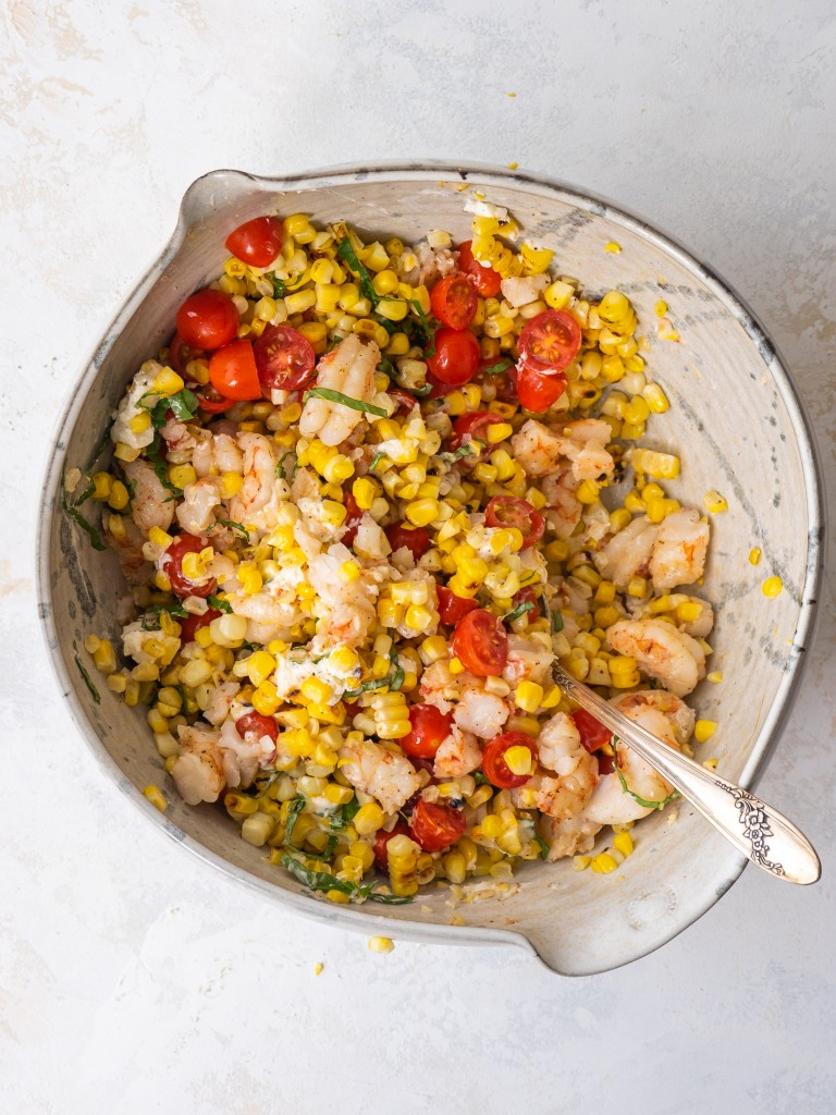 Grilled shrimp and corn salad in a mixing bowl