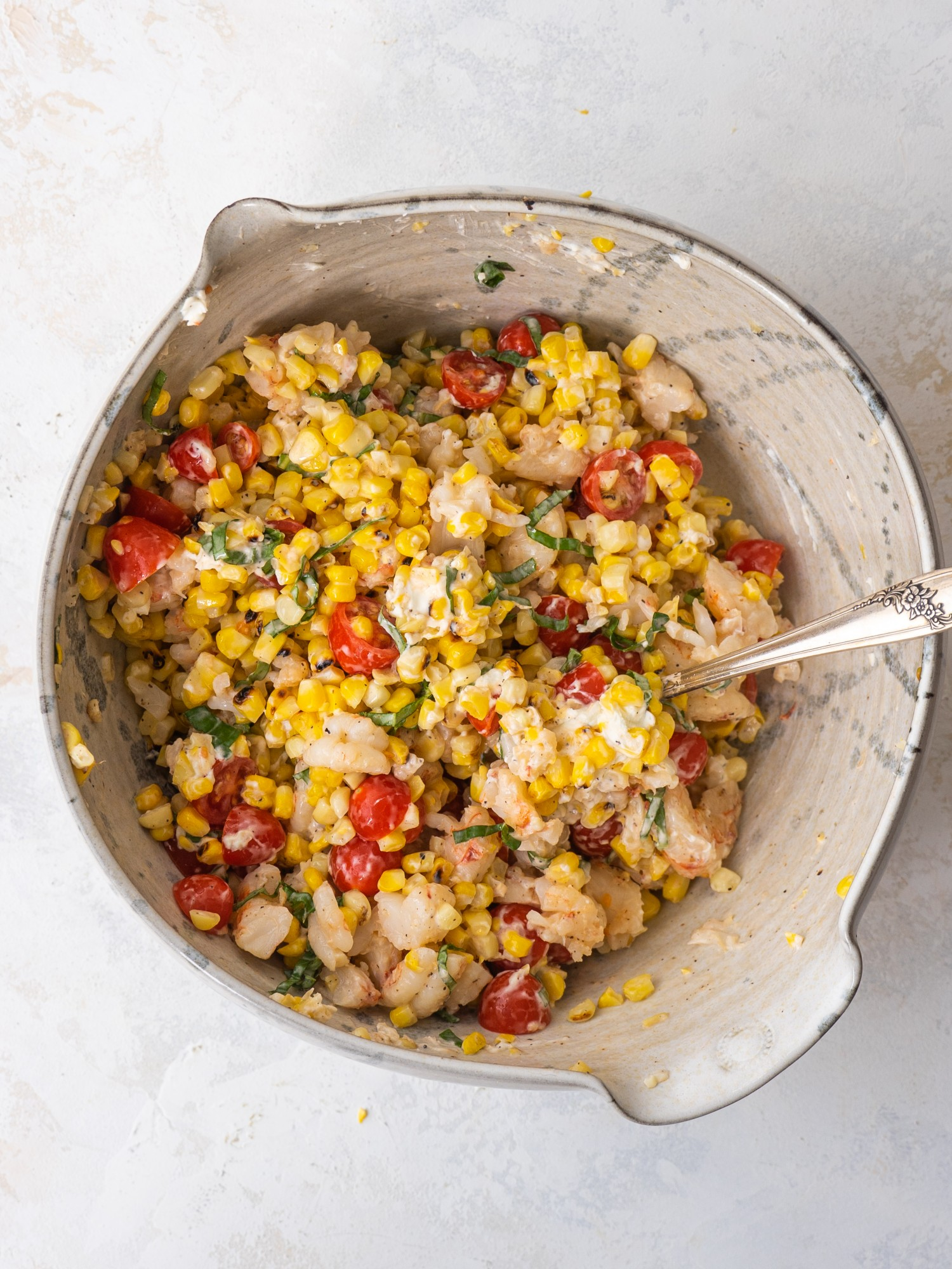 Creamy grilled corn salad with shrimp and tomatoes in a mixing bowl