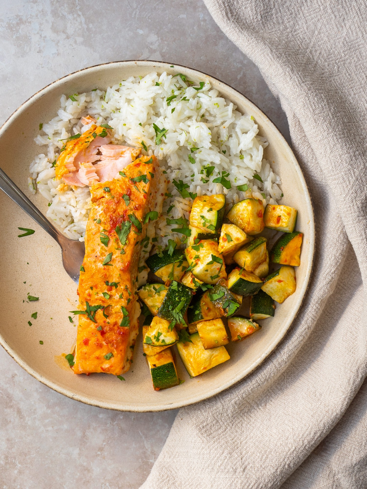 Above view of a serving of harissa salmon with a bite out of it with roasted zucchini and rice