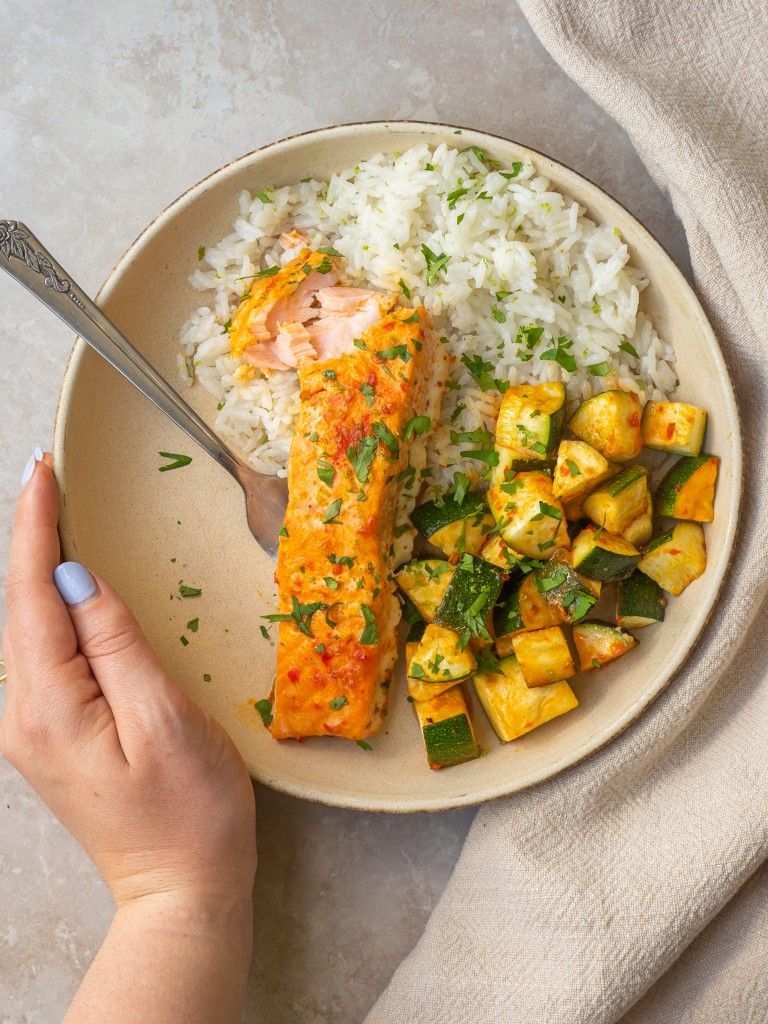 Above view of a hand around a plate of baked harissa salmon with harissa roasted zucchini and rice