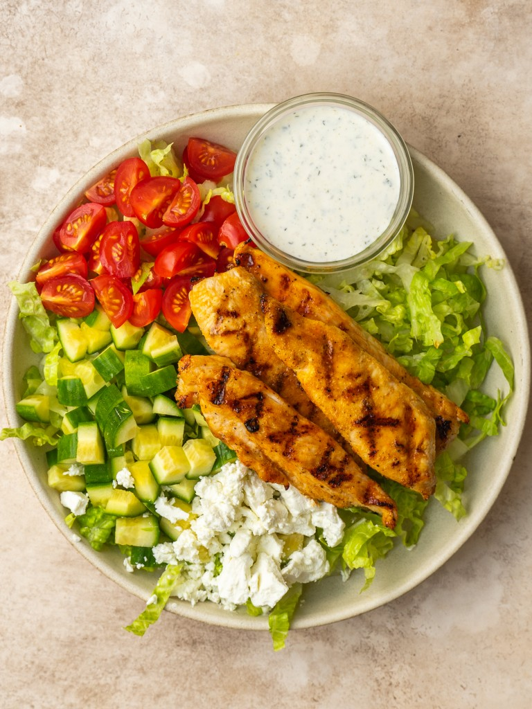 Above view of a salad with grilled buffalo chicken tenders on top