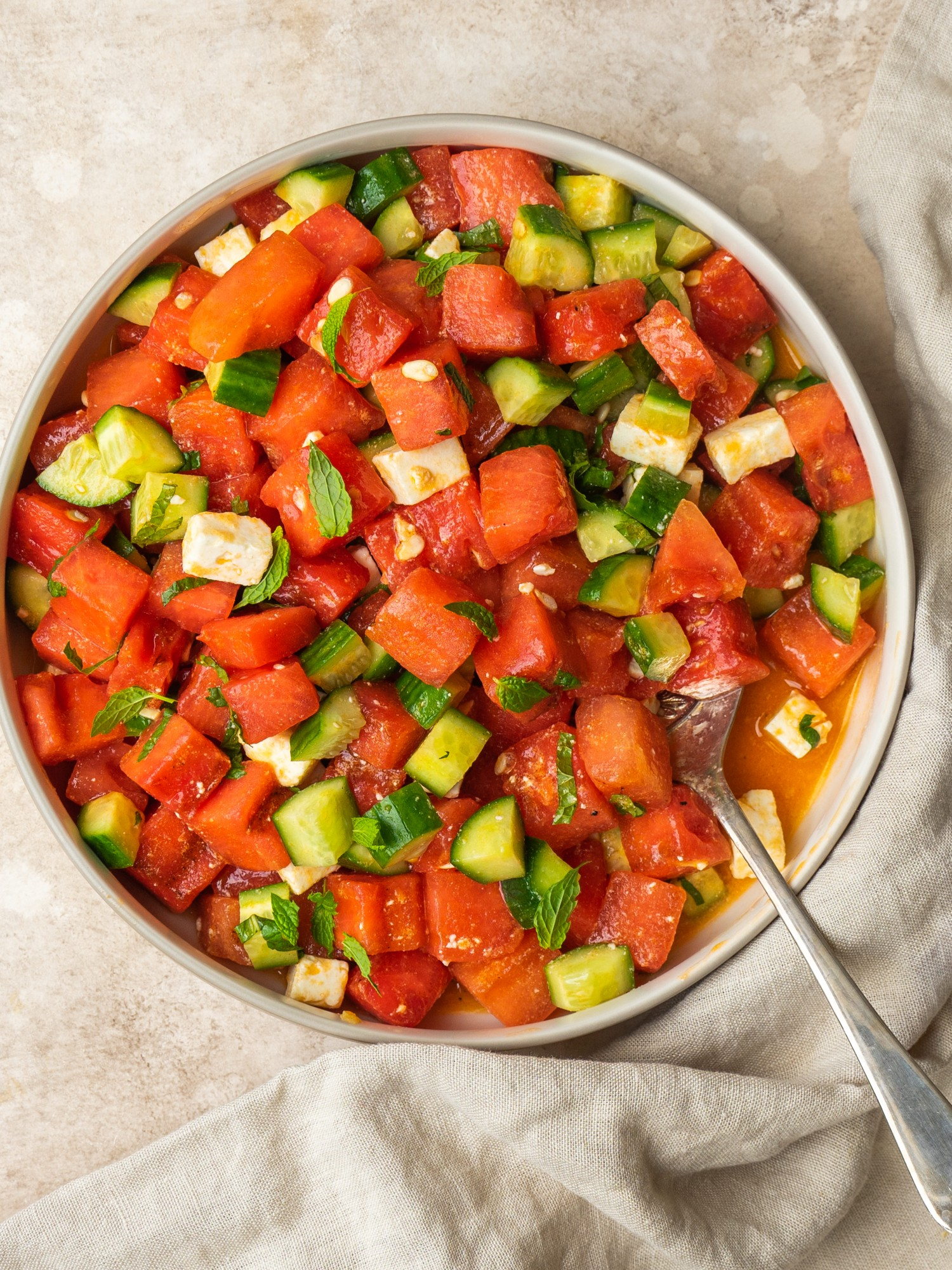 Grilled watermelon salad in a serving bowl with a serving spoon in it