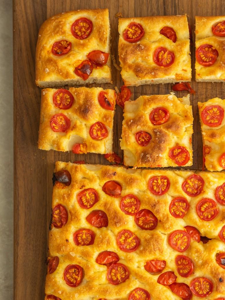 Slices of no knead tomato focaccia on a cutting board