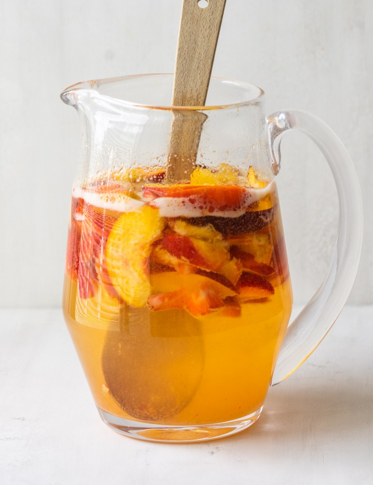 Side view of white wine peach sangria in a pitcher