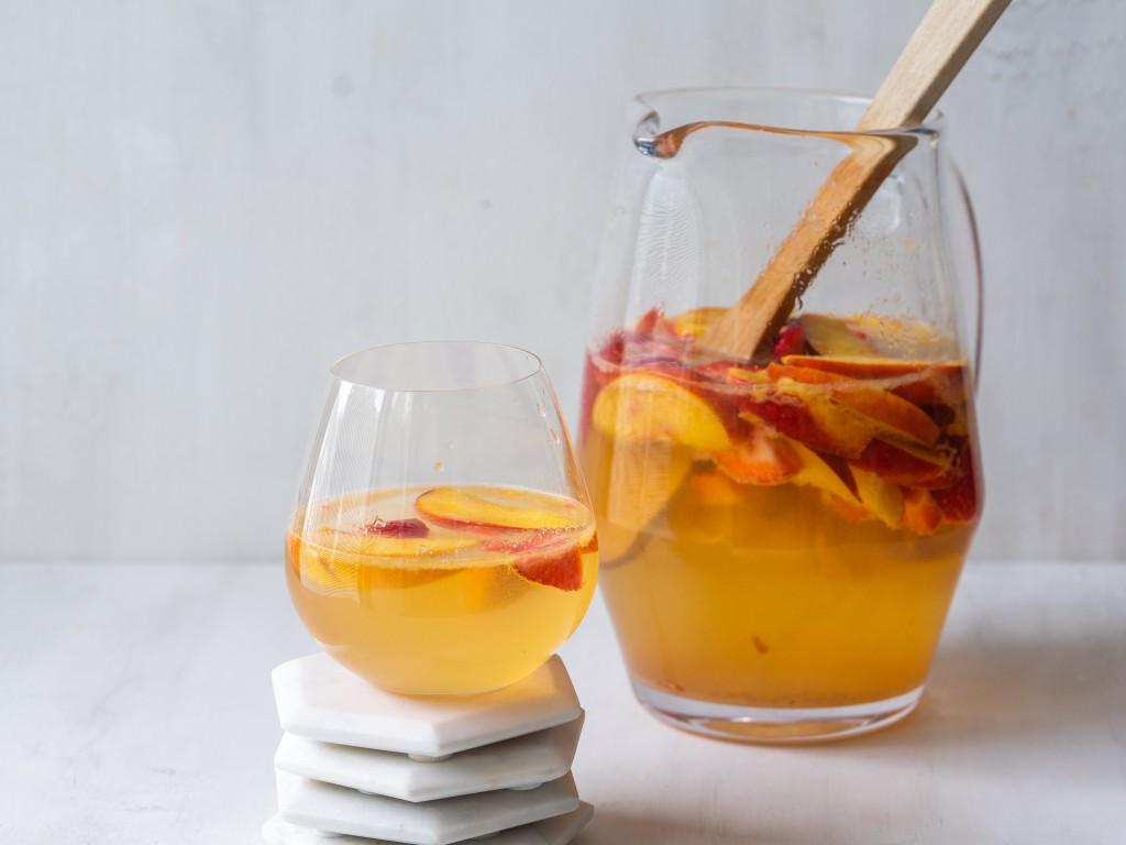 Side view of a pitcher of peach sangria with a glass of sangre