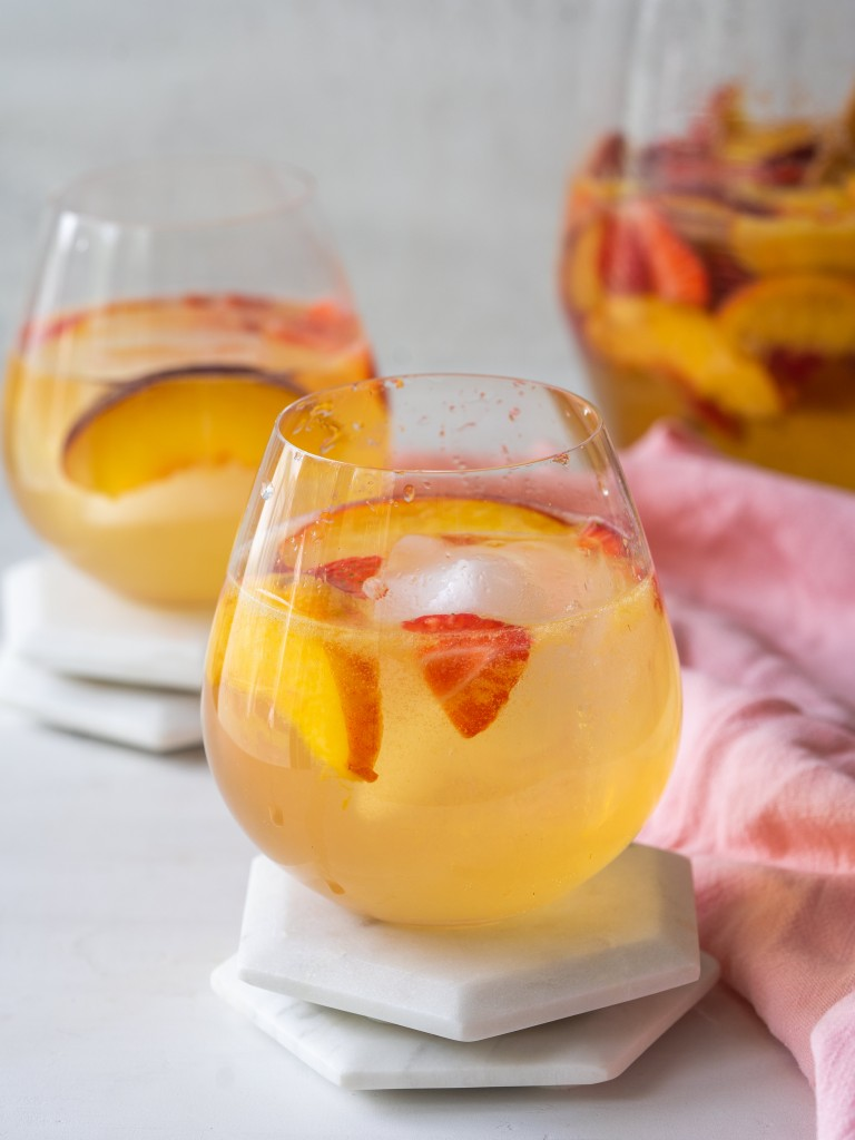Close up side view of a glass of peach sangria made with white wine and strawberries
