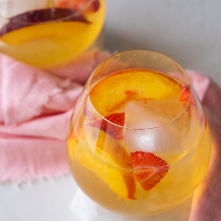 Three quarter view of white wine sangria with strawberries and peaches