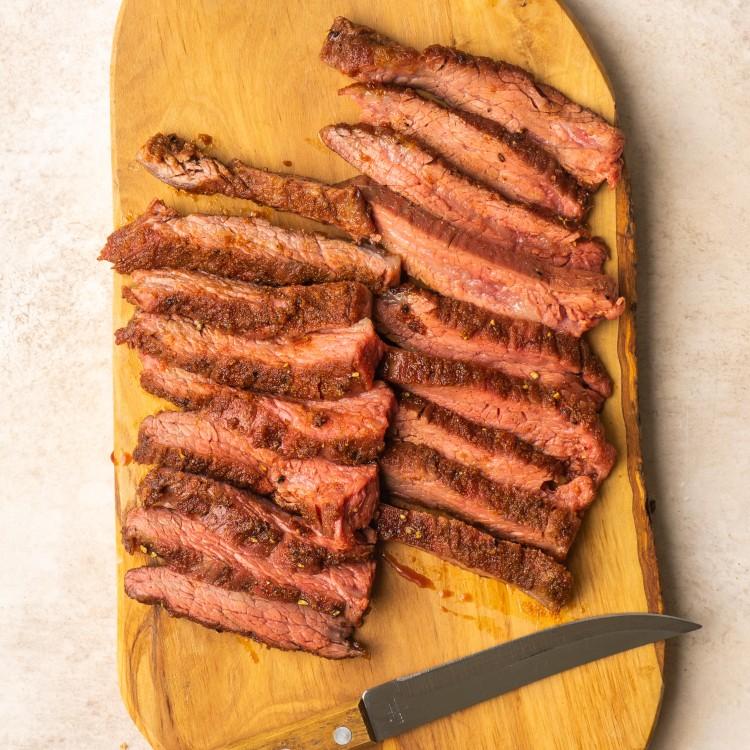 Sliced air fryer flank steak on a cutting board with a sharp knife