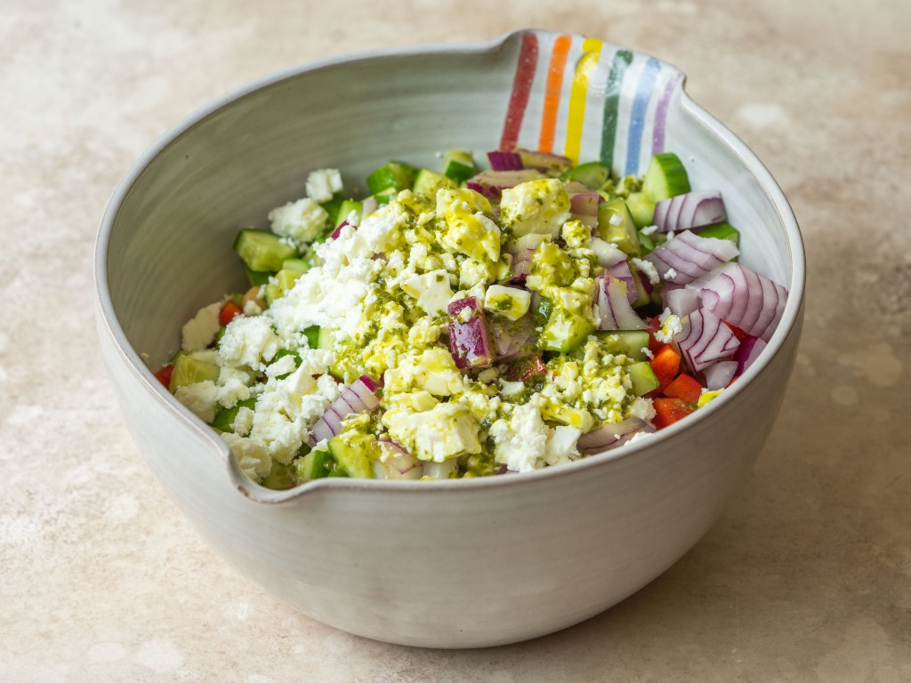 Quinoa and chickpea salad in a mixing bowl topped with feta and lemon basil vinaigrette