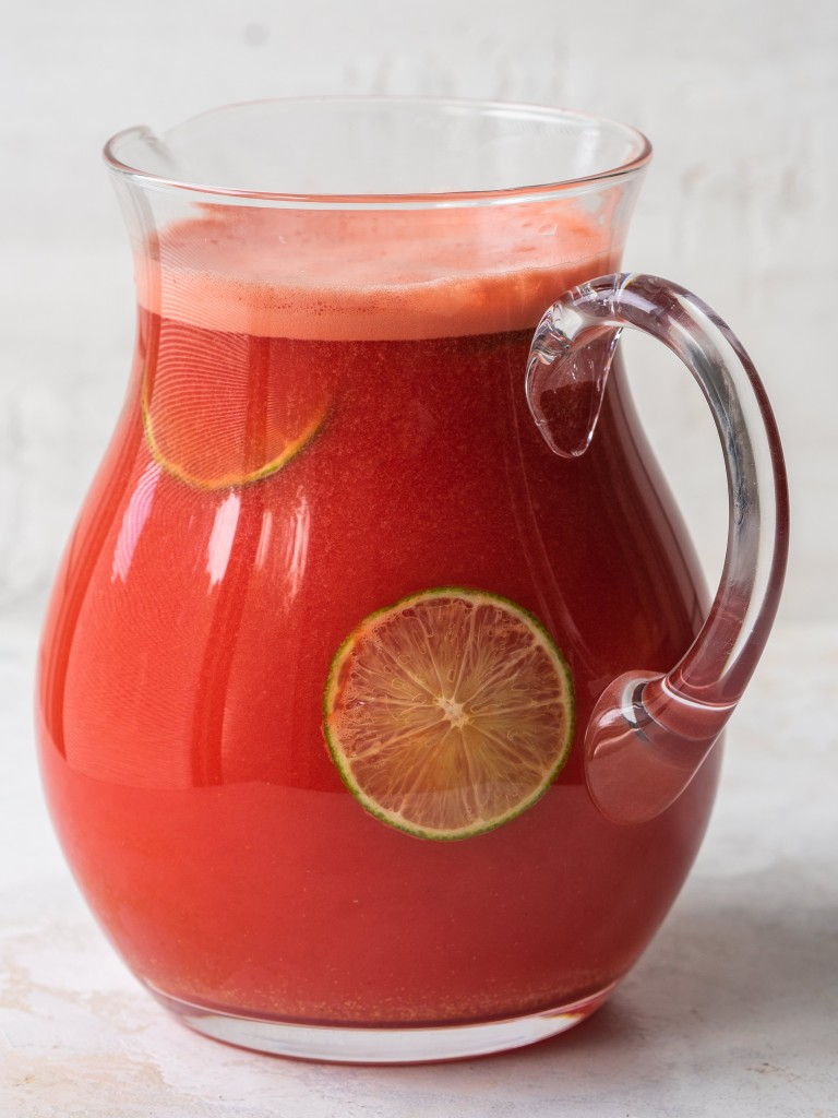 Watermelon vodka drink in a serving pitcher with lime slices