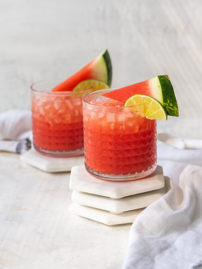 Two watermelon vodka cocktails with watermelon and lime garnish