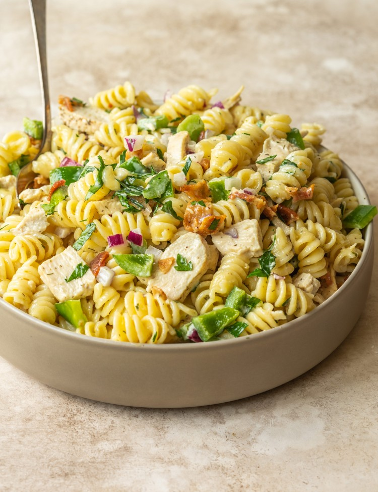 Three quarter view of a chicken bacon and ranch with pasta, parsley, bell pepper and red onion