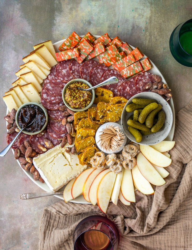fall charcuterie board with glasses of wine