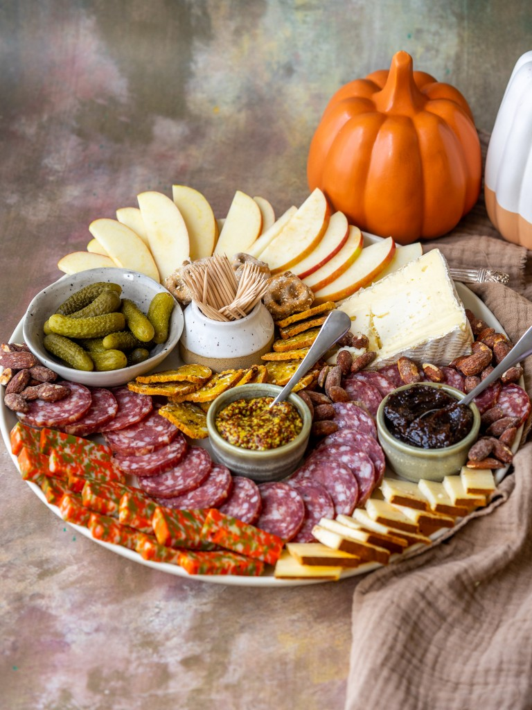 Three quarter view of a charcuterie board with pumpkins behind it