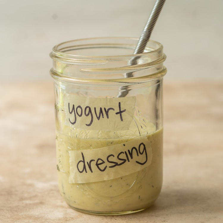 Side view of yogurt dressing in a mason jar with a whisk in it