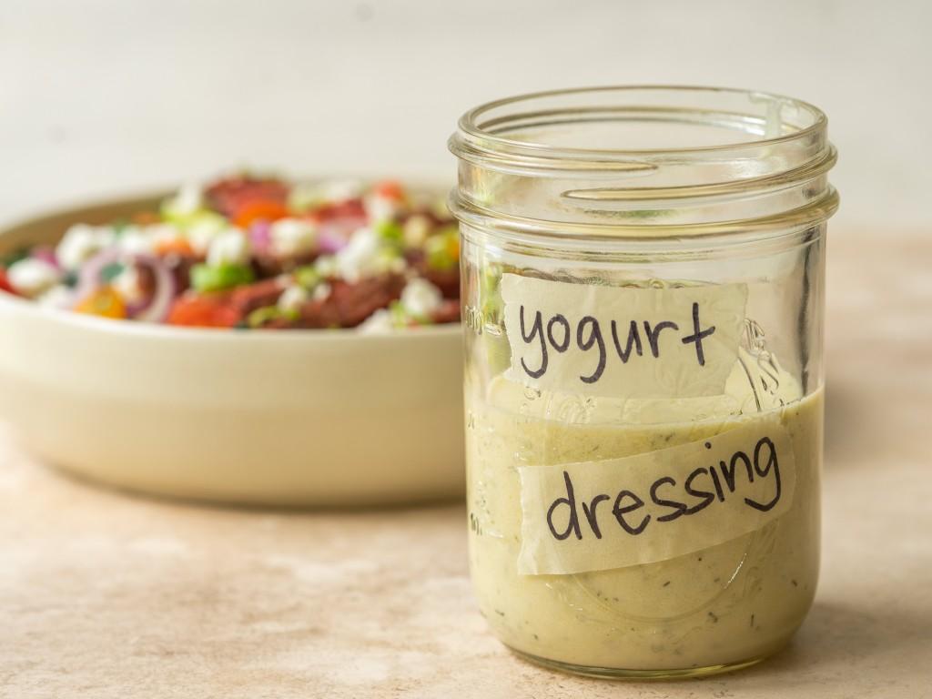 Side view of Greek yogurt salad dressing in a mason jar in front of a salad