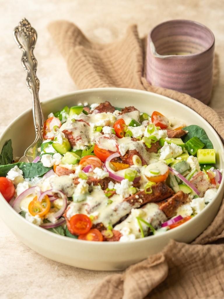 Three quarter view of a salad topped with a Greek yogurt salad dressing