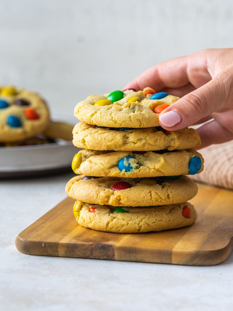 Side view of a hand grabbing a sugar cookie m&m off a stack