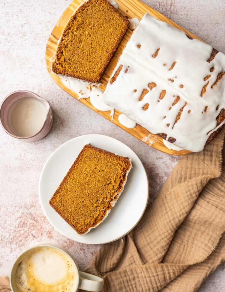Slice of spice cake on a serving plate next to extra spice cake frosting
